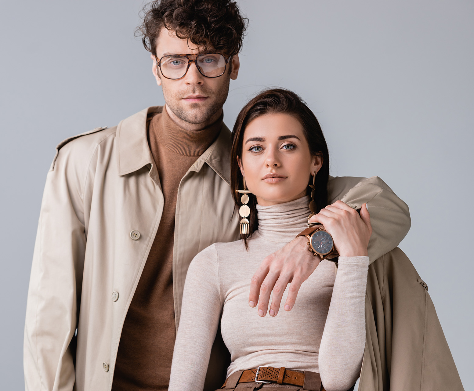 handsome, trendy man embracing stylish woman while looking at camera isolated on grey